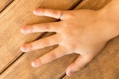 De hand van een klein meisje met een gouden ring op haar vinger Op wo Stock Foto