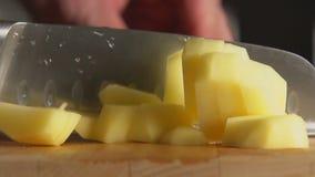 De hand van een kok snijdt een aardappel door een mes op een raad stock footage