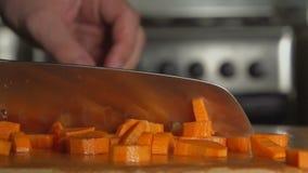 De hand van een kok snijdt een wortel door een mes stock footage