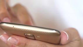 De hand van een meisje typt een mobiel bericht op het smartphonescherm De handen van vrouwen houden smartphone en browser stock video