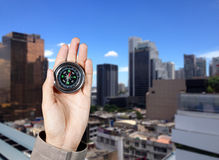 De hand van een mens die een magnetisch kompas over een stadsgebouwen houden Stock Afbeeldingen