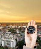De hand van een mens die een magnetisch kompas over een stadsgebouwen houden Royalty-vrije Stock Foto
