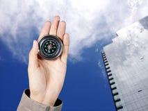 De hand van een mens die een magnetisch kompas over een stadsgebouwen houden Stock Foto's