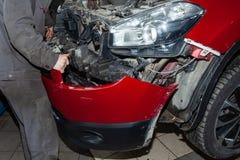 De hand van een mens die of de voorbumper aanzetten verwijderen uit een rode moderne auto in een voertuigreparatiewerkplaats Indu stock fotografie