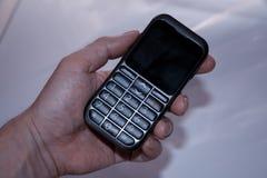 De hand van een mens houdt een oude drukknoptelefoon royalty-vrije stock foto's