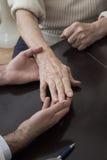 De hand van een oude vrouw op een donkere achtergrond Stock Fotografie