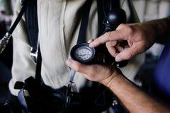 De hand van een Roemeense militaire zeeman houdt een manometer stock fotografie