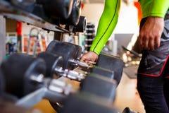 De hand van een sterke mens neemt een zware domoor in de gymnastiek Stock Fotografie