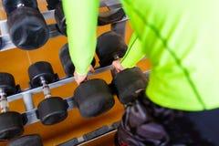 De hand van een sterke mens neemt een zware domoor in de gymnastiek Stock Afbeelding