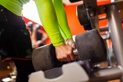 De hand van een sterke mens neemt een zware domoor in de gymnastiek Royalty-vrije Stock Foto
