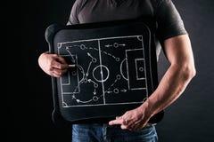 De hand van een voetbal of het voetbal speelt bus trekkend een tactiek van voetbalspel met wit krijt op bord bij kleedkamer tijde royalty-vrije stock afbeeldingen