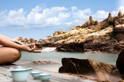 De hand van een vrouw die in een yoga mediteren stelt langs op het rotsachtige strand royalty-vrije stock foto's