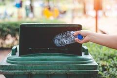 De hand van een vrouw die huisvuil in het afval dumpt Stock Foto's