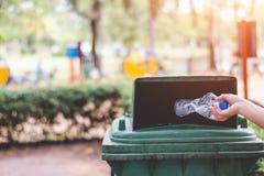 De hand van een vrouw die huisvuil in het afval dumpt Stock Fotografie