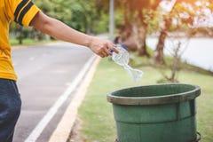 De hand van een vrouw die huisvuil in het afval dumpt Stock Afbeeldingen