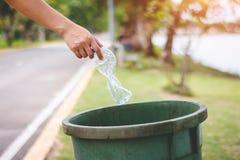 De hand van een vrouw die huisvuil in het afval dumpt Royalty-vrije Stock Fotografie