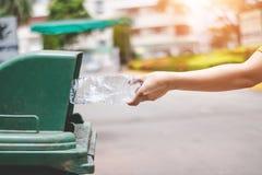 De hand van een vrouw die huisvuil in het afval dumpt Royalty-vrije Stock Foto