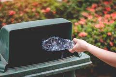 De hand van een vrouw die huisvuil in het afval dumpt Royalty-vrije Stock Foto's