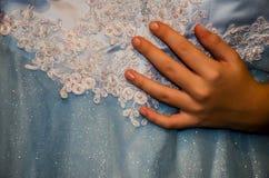 De hand van een vrouw en een mooie, blauwe kleding stock afbeelding