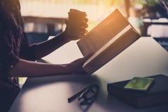 De hand van een zakenman die een kop van koffie houden en a lezen royalty-vrije stock fotografie