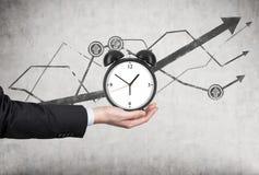 De hand van een zakenman houdt een wekker Er zijn een het groeien lijngrafieken achter de wekker Een concept tijdbeheer of Stock Foto
