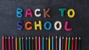 De hand van de eindemotie - het gemaakte plasticine van letters voorzien terug naar school op het bord De regenboog van het pretb stock video
