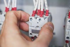 De hand van elektricien installeert pakketschakelaar met verbonden dicht omhoog draden in elektrisch controlebord royalty-vrije stock fotografie