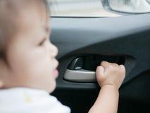 De hand van het babymeisje ` s ongeveer om het deurhandvat van een bewegende auto van binnenuit te trekken stock afbeeldingen