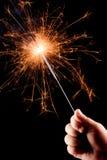 De hand van het kind, die een brandend sterretje houdt. Stock Fotografie