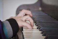 De hand van het kind het spelen piano Stock Foto