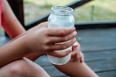 De hand van het kind houdt een glasmelk Stock Foto's