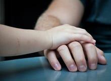 De hand van het kind legt bovenop volwassen hand Stock Afbeelding