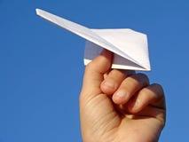 De hand van het kind met document vliegtuig stock foto