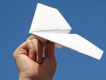 De hand van het kind met document vliegtuig stock fotografie
