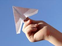 De hand van het kind met document vliegtuig royalty-vrije stock afbeelding