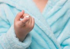 de hand van het kind met room op een vinger Stock Afbeeldingen