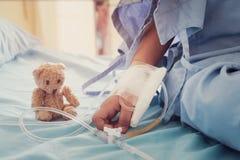 De hand van het kind van de moederholding die koortspatiënten in het ziekenhuis aan gi stock foto