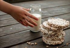 De hand van het kind neemt naar huis melk smakelijk knäckebrood op houten lijst als achtergrond Royalty-vrije Stock Afbeelding