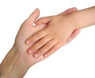 De hand van het kind op de hand van de moeder die op wit wordt geïsoleerdr Stock Foto