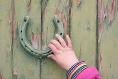 De hand van het kind op deurkloppers Stock Foto
