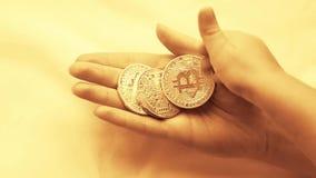 De hand van het kind zet een muntstuk bitcoin in de hand van een jonge vrouw, en neemt het dan Crypto munt in de handen stock videobeelden