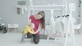 De hand van het leuke het tandjes krijgen van het babymeisje het bijten mamma thuis stock videobeelden