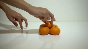 De hand van het meisje neemt mandarin stock videobeelden