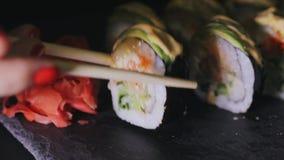 De hand van het meisje neemt sushi gebruikend eetstokjes stock footage