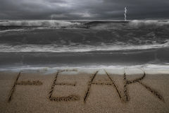 De hand van het vreeswoord op zandstrand wordt geschreven met stormachtige oceaan die Royalty-vrije Stock Fotografie