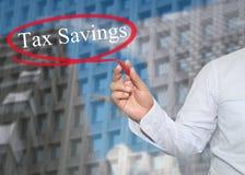 De hand van jonge zakenman schrijft de Besparingen van de woordbelasting op skyscrap royalty-vrije stock foto's