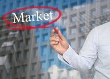 De hand van jonge zakenman schrijft de woordmarkt op wolkenkrabbers B royalty-vrije stock foto