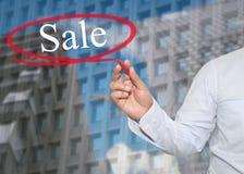 De hand van jonge zakenman schrijft de woordverkoop op wolkenkrabbersbac stock foto