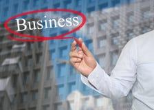 De hand van jonge zakenman schrijft de woordzaken op wolkenkrabbers stock fotografie