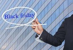 De hand van jonge zakenman schrijft het woord Black Friday op skyscra stock foto